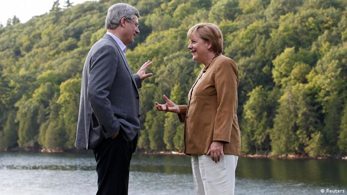 Canada's Prime Minister Stephen Harper (L) talks with Germany's Chancellor Angela Merkel at Harrington Lake, Harper's official country retreat, in Gatineau Park, Quebec August 15, 2012. Merkel is on an official visit to Canada from August 15-16. REUTERS/Chris Wattie (CANADA - Tags: POLITICS)