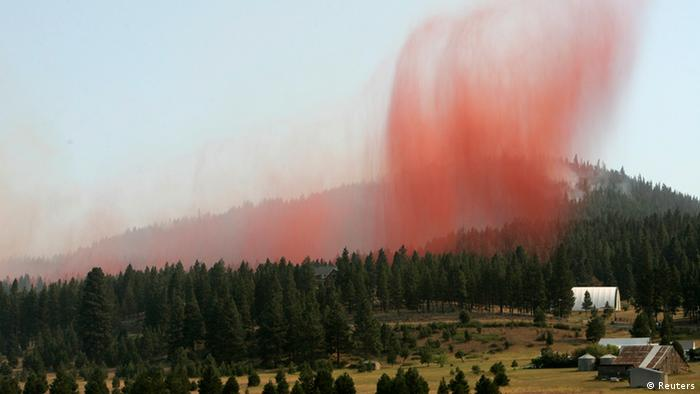 Orange fire retardant is dumped from a firefighting tanker plane onto trees near homes threatened by the Taylor Bridge Fire outside of Cle Elum, Washington, August, 15, 2012(REUTERS/Robert Sorbo)