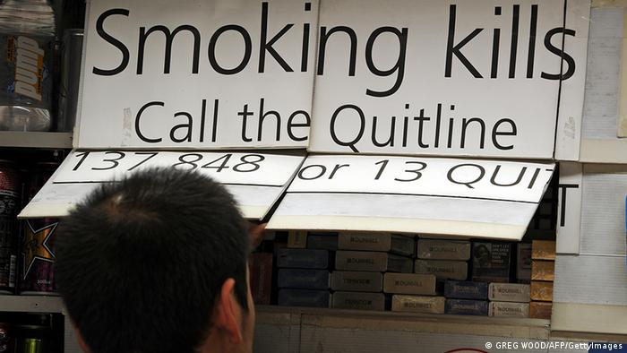 A kiosk worker (below) looks at cigarette packets which are kept covered up by law in central Sydney on August 15