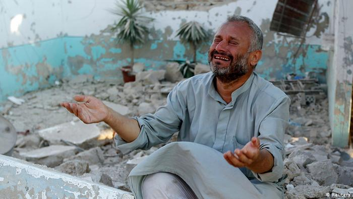 A man cries in front of houses destroyed during the Syrian Air Force air strike on Azaz