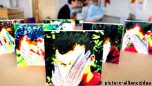 Verfremdete Bilder eines Kindes mit Schulangst stehen am Donnerstag (14.04.2005) in der Klinikschule in Köln auf einem Tisch, während eine Lehrerin im Hintergrund am Computer arbeitet. Die Klinikschule der Kinder- und Jugendpsychiatrie der Universität Köln ist für viele einst hoffnungsvoll gestartete Kinder nach krassem Leistungsabfall aus Angst vor Versagen, Mobbing und monatelanger Schulverweigerung eine letzte Chance. Foto: Rolf Vennenbernd dpa/lnw (zu dpa-KORR: Angst vor Schule geht um - Experten sehen beginnende Epidemie vom 26.04.2005) +++(c) dpa - Bildfunk+++
