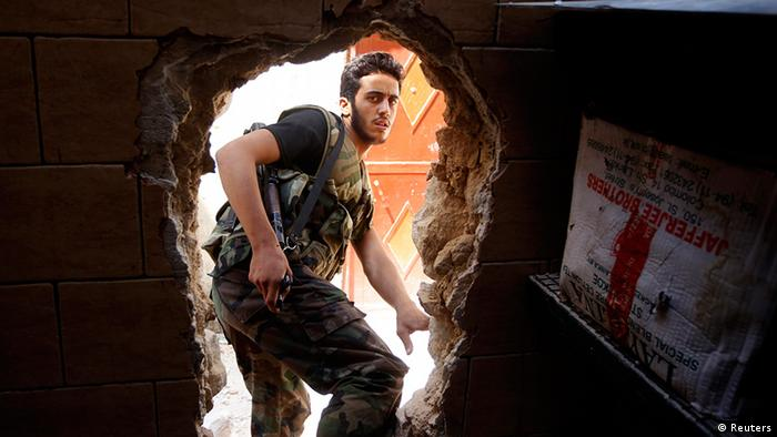 A Free Syrian Army fighter walks through a hole in wall during clashes in Aleppo August 16, 2012. REUTERS/Goran Tomasevic (SYRIA - Tags: CIVIL UNREST CONFLICT POLITICS MILITARY)