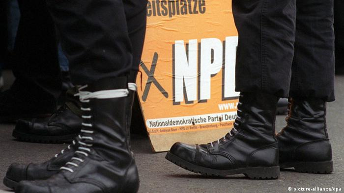 An NPD election placard displayed between dark boots of NPD supporters