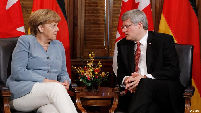 Canada's Harper seated in discussion with Chancellor Merkel in Ottawa. In the background: Flags of both nations