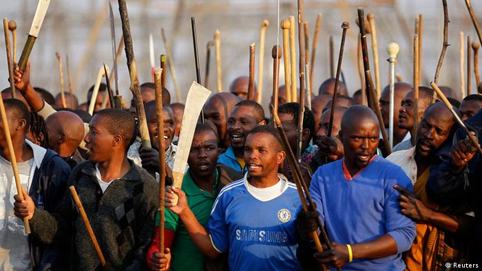 Striking miners chant slogans outside a South African mine in Rustenburg (REUTERS/Siphiwe Sibeko)