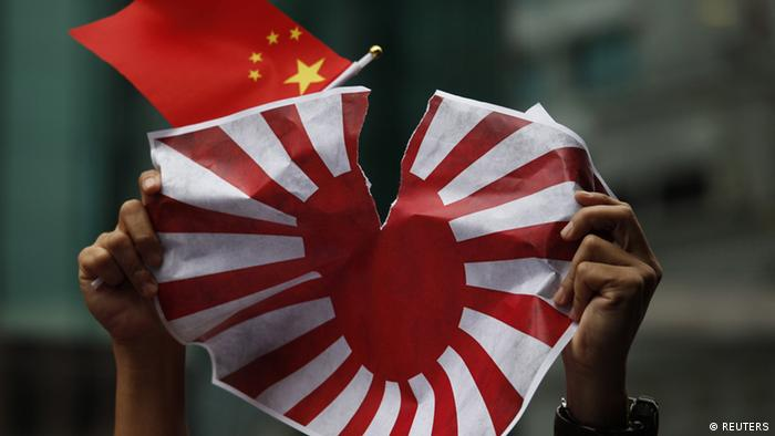 A copy of Japan's military flag is torn by a protester holding China's national flag outside the Japanese embassy in Hong Kong August 16, 2012, after 14 Chinese activists were detained by the Japanese authorities at the Senkaku or Diaoyu Islands on Wednesday.
