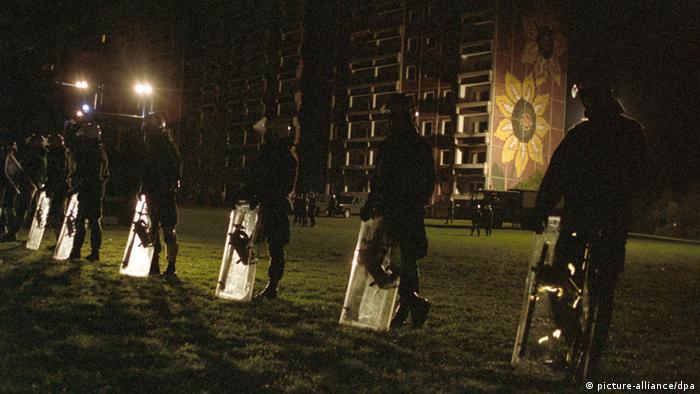 Polizisten schirmen das bereits geräumte Asylbewerberheim in Rostock ab (Foto: dpa)