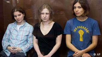 Feminist punk group Pussy Riot members, Nadezhda Tolokonnikova, right, Maria Alekhina, center, and Yekaterina Samutsevich sit in a glass cage at a court room in Moscow (Foto:Misha Japaridze/AP/dapd)