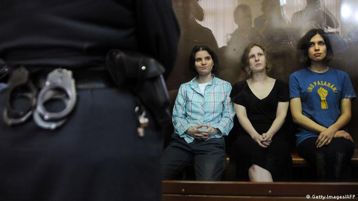 Members of the all-girl punk band 'Pussy Riot' Nadezhda Tolokonnikova (R), Maria Alyokhina (R) and Yekaterina Samutsevich (C) sit in a glass-walled cage during a court hearing in Moscow on Agust 17, 2012. A Moscow court will pass judgement Friday on three women from a tiny punk band who captured global attention by defying the Russian authorities and ridiculing President Vladimir Putin in a church. Pussy Riot release rallies have stretched from Sydney to New York as a growing list of celebrities joined ex-Beatle Paul McCartney and pop icon Madonna in a campaign directed against Putin's crackdown on most dissent. AFP PHOTO / ANDREY SMIRNOV (Photo credit should read ANDREY SMIRNOV/AFP/GettyImage