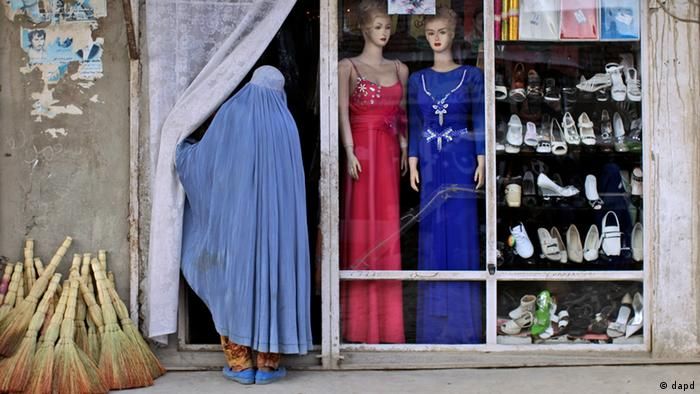 An Afghan woman looks inside a shop displaying new models of clothes and shoes for the upcoming Eid-al-Adha festival, in Kabul, Afghanistan, Saturday, Nov. 5, 2011.