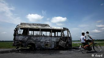 Two cyclists ride past a burnt vehicle in Assam on August 16, 2012