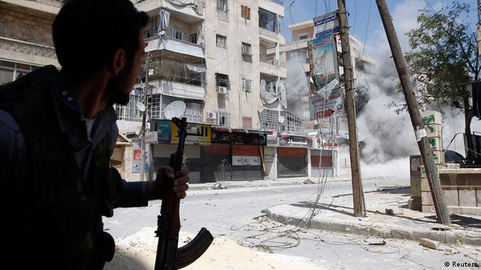 A Free Syrian Army fighter runs for cover as a Syrian Army tank shell hits a building across a street during clashes in the Salaheddine neighbourhood of central Aleppo August 17, 2012. REUTERS/Goran Tomasevic (SYRIA - Tags: CIVIL UNREST CONFLICT MILITARY POLITICS)