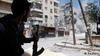 A Free Syrian Army fighter runs for cover as a Syrian Army tank shell hits a building across a street during clashes in the Salaheddine neighbourhood of central Aleppo