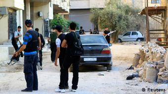 Waasi wa Jeshi Huru la Syria wakillinda mitaa waliyoiteka mjini Damascus.