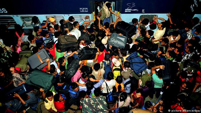 Hundreds of migrant students and workers from northeastern part of Assam scramble to board a train at the city railway station