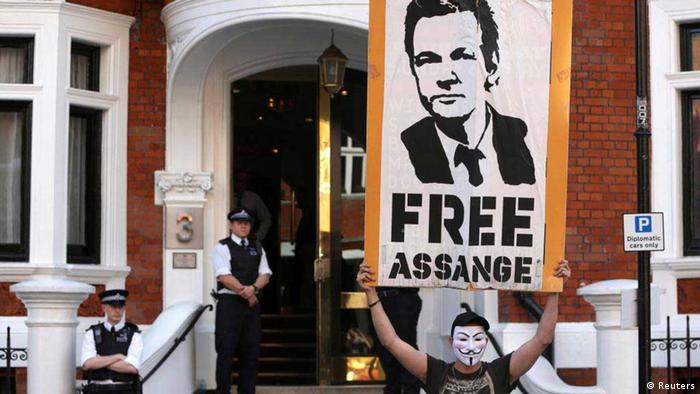 A protestor holds a poster of Wikileaks founder Julian Assange outside Ecuador's embassy in London REUTERS/Neil Hall
