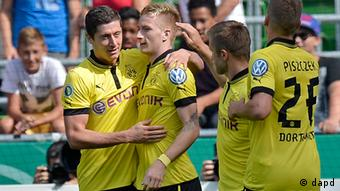 Dortmund's Marco Reus, 2nd from left, is celebrated after scoring during the German soccer cup match between FC Oberneuland and Borussia Dortmund in Bremen, Saturday, Aug. 18, 2012.