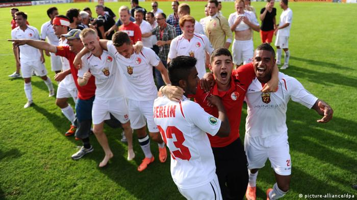 The players from Berliner AK 07 celebrate their shock win over Hoffenheim in the German Cup