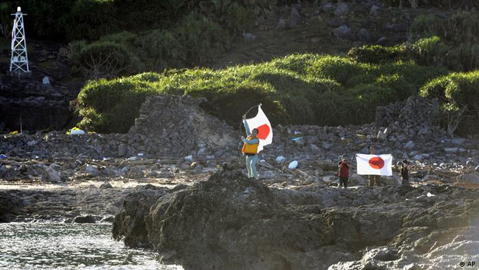 Japanese activists hold the national flags on Uotsuri island, one of the islands of Senkaku in Japanese and Diaoyu in Chinese, in East China Sea, Sunday, Aug. 19, 2012. Japan's Coast Guard says a group of Japanese activists have landed on Uotsuri, one of a group of islands at the center of an escalating territorial dispute with China. (Foto:Kyodo News/AP/dapd) JAPAN OUT, MANDATORY CREDIT, NO LICENSING IN CHINA, HONG KONG, JAPAN, SOUTH KOREA AND FRANCE