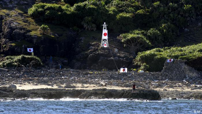 Japanese activists wave the national flag in front of a lighthouse on Uotsuri island, one of the islands of Senkaku in Japanese and Diaoyu in Chinese, in East China Sea, Sunday, Aug. 19, 2012. A group of Japanese activists Aktion japanischer Aktivisten auf den Senkaku-Inseln im Ostchinesischen Meer. (Foto:Kyodo News/AP/dapd)