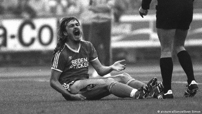 Ewald Lienen sitting on the pitch deploring the gash in his thigh +++ picture-alliance / Sven Simon