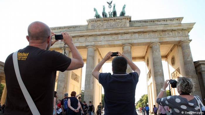 Tourists take photos of the Brandenburg Gate