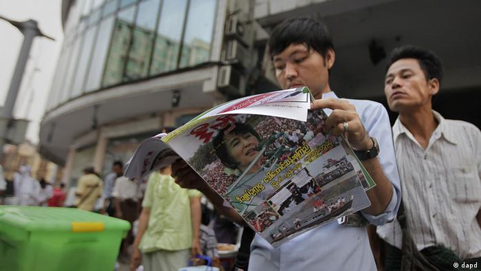 In this photo taken on April 2, 2012, a Myanmar man takes a peek at a newspaper as another looks on in Yangon, Myanmar.