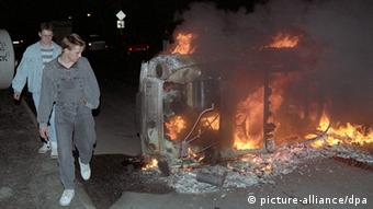 People walk by a burning car during the riots of August 1992