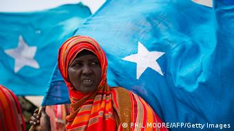 A woman stands holding the Somali flag (Photo: PHIL MOORE/AFP/Getty Images)