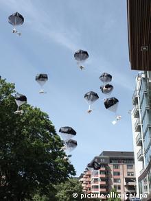 Teddy bears stream through the air on parachutes