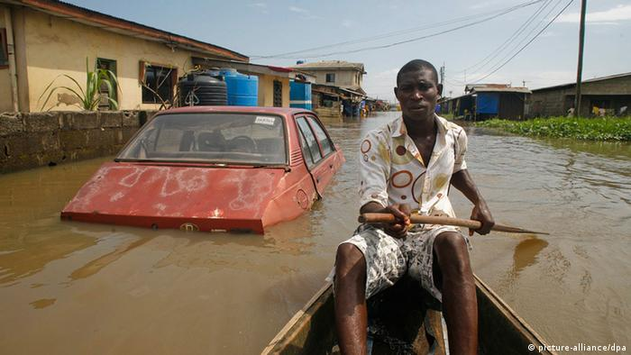 A man in a canoe passes semi-submerged houses and a car