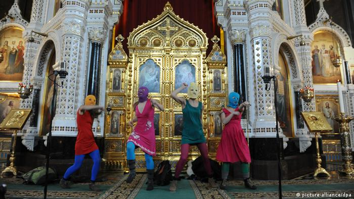 Masked members of Pussy Riot feminist punk group perform during their 'flashmob'-style protest inside Moscow's Cathedral of Christ the Savior