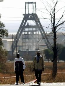 Miners walk away from mine shaft works at the Gold Fields Driefontein mine, southwest of Johannesburg