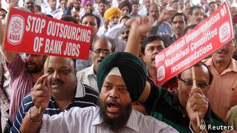 A bank employee shouts slogans while holding placards at a rally during a two-day strike in the northern Indian city of Chandigarh