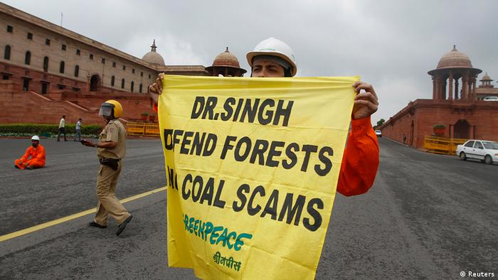 A Greenpeace activist holds a banner near parliament in New Delhi to protest coalgate
