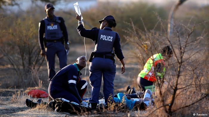 Police attend to injured mine workers in Marikana