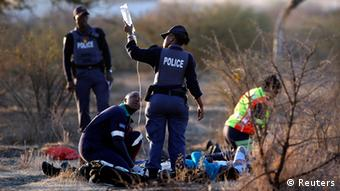 A paramedic receives help from a policewomen as he tends to the injured after protesting miners were shot outside a South African mine