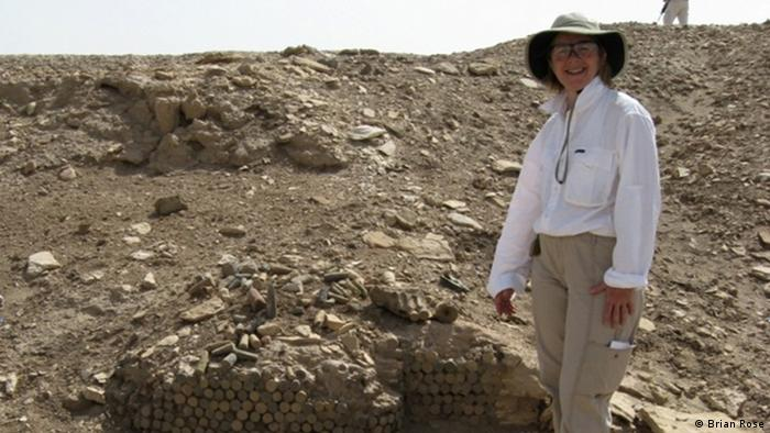 Archeologist Laurie Rush in Uruk in Iraq, standing in front of the remains of an ancient stone cone mosaic tower