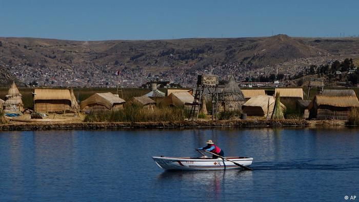 A woman rows a boat as she heads one of the Uros floating islands on the Titicaca Lake in Puno, Peru