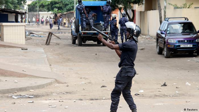 A riot policeman attempts to disperse opposition protesters during clashes in Togo's capital Lome, August 21, 2012. Police in Togo fired tear gas and rubber bullets to try to disperse thousands of opposition protesters in the capital Lome on Tuesday, as tensions over upcoming legislative elections boiled over. REUTERS/Noel Kokou Tadegnon (TOGO - Tags: POLITICS CIVIL UNREST)