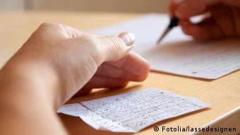 A student's hands are seen as he's copying something from a hidden note. (Photo: Fotolia/lassedesignen #34607034)