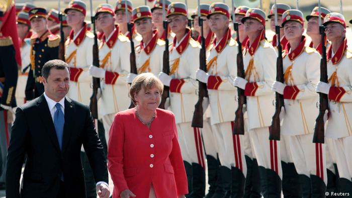 Moldova's Prime Minister Vladimir Filat (L) and Germany's Chancellor Angela Merkel inspect the honour guard in Chisinau