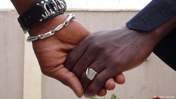 Two Black men holding hands