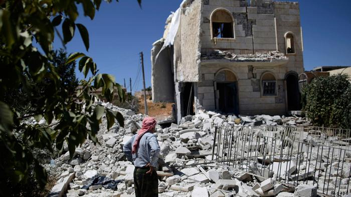 Syrian Nasif Hashoum, 54, looks at the rubble of a house destroyed in a Syrian government airstrike in Anadan, on the outskirts of Aleppo, Syria, Wednesday, Aug. 22, 2012. (Foto:Muhammed Muheisen/AP/dapd)
