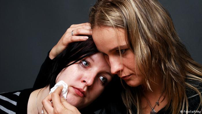 Ein Mädchen hält ein anderes weinendes Mädchen im Arm und trocknet ihre Tränen.