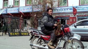 FILE - In this Feb. 27, 2012 file photo, a Tibetan man rides a motorbike past a group of Chinese paramilitary policemen standing guard near barricades set up along the main street of Aba county seat, in China's Sichuan province. In Tibet, the horrific has become normal. More than two dozen Tibetans, many in their teens or 20s, have set themselves on fire since early 2011 in an unprecedented series of suicide-protests. (Foto:Gillian Wong, File/AP/dapd)