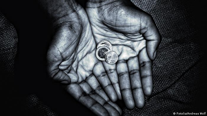 A pair of cupped hands shown close-up, holding a few euro coins