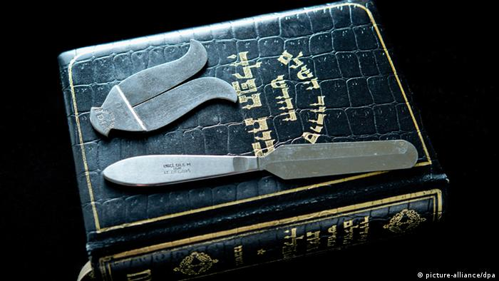 Tools of circumcision sit atop a Hebrew language version of the Old Testament