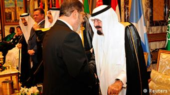 Saudi Arabia's King Abdullah (R) speaks with Egypt's President Mohamed Mursi at the opening ceremony of the Organisation of Islamic Conference (OIC) summit in Mecca August 14, 2012. REUTERS/Saudi Press Agency/Handout (SAUDI ARABIA - Tags: POLITICS ROYALS) FOR EDITORIAL USE ONLY. NOT FOR SALE FOR MARKETING OR ADVERTISING CAMPAIGNS. THIS IMAGE HAS BEEN SUPPLIED BY A THIRD PARTY. IT IS DISTRIBUTED, EXACTLY AS RECEIVED BY REUTERS, AS A SERVICE TO CLIENTS