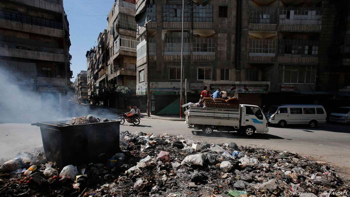Smoke clears up after residents burn rubbish at the center of Aleppo cityl